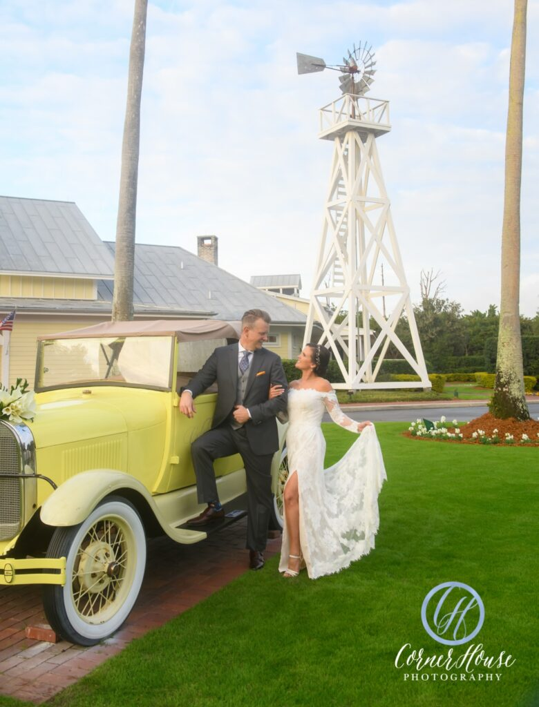 Couple standing with vintage car in front of windmill