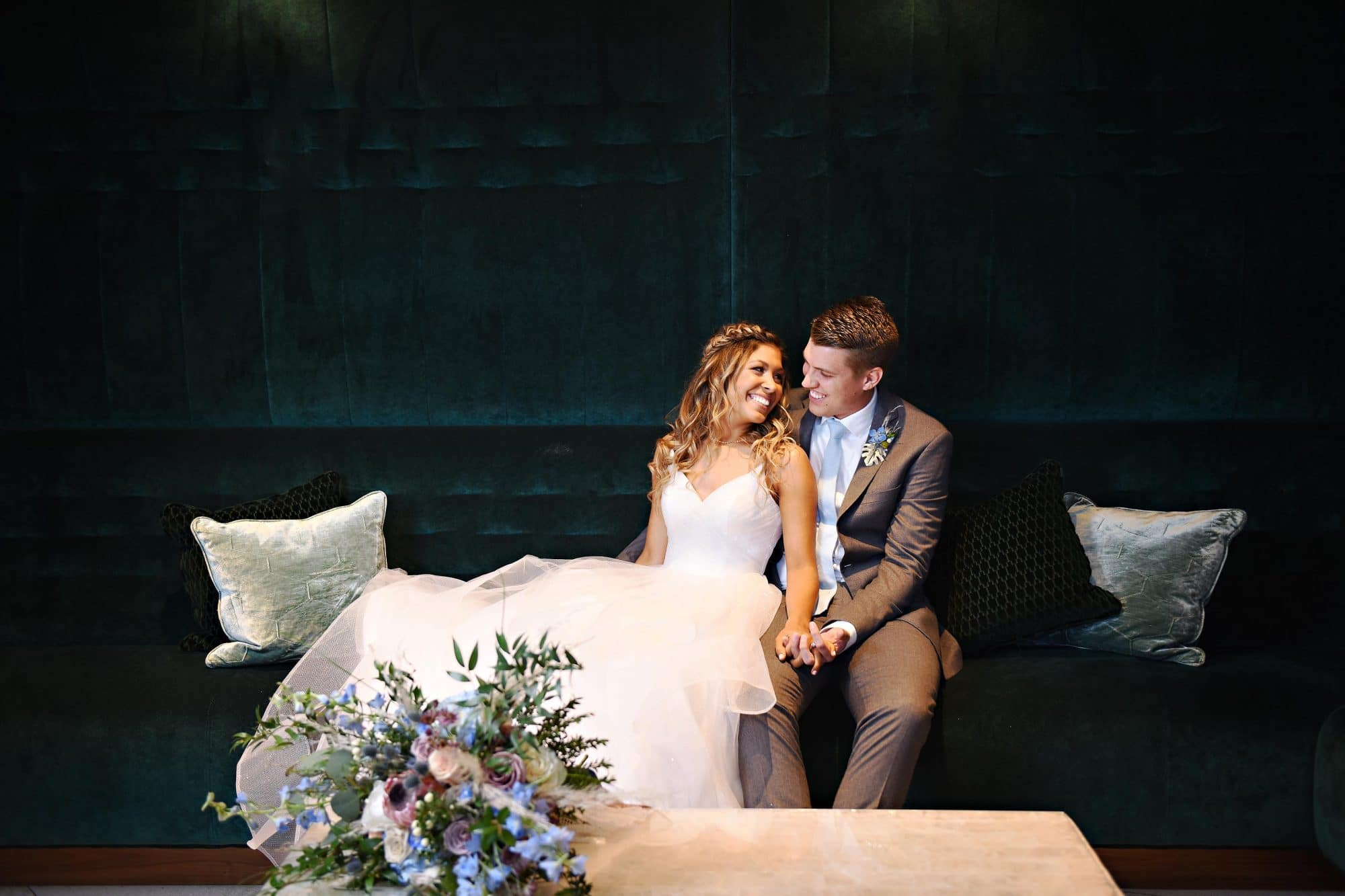 bride and groom on dark couch and dark wall