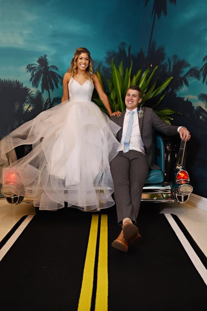 Bride and groom in couch shaped like a retro car.