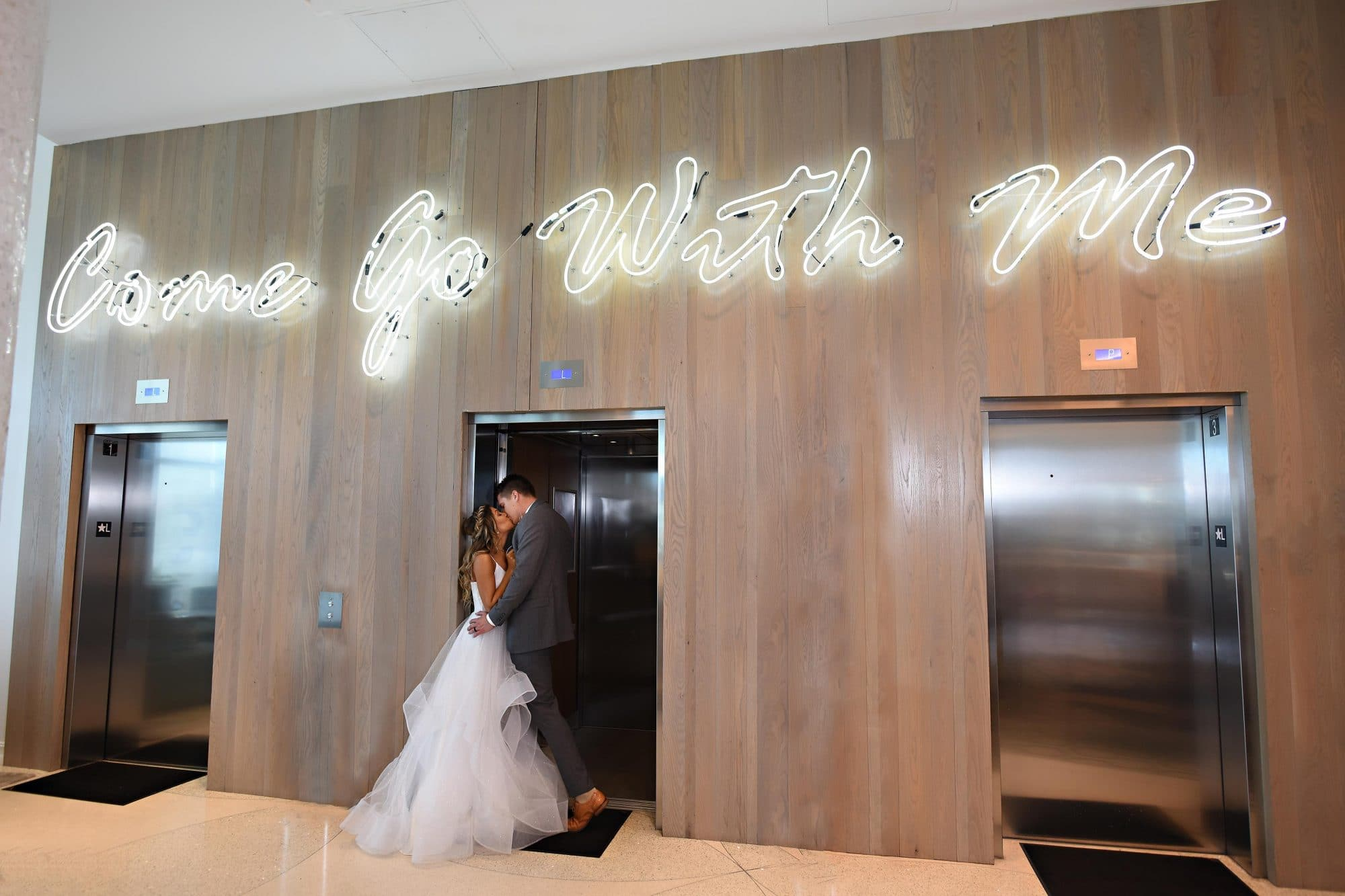 "bride and groom kissing in elevator with neon sign above reading ""Come Go With Me"""