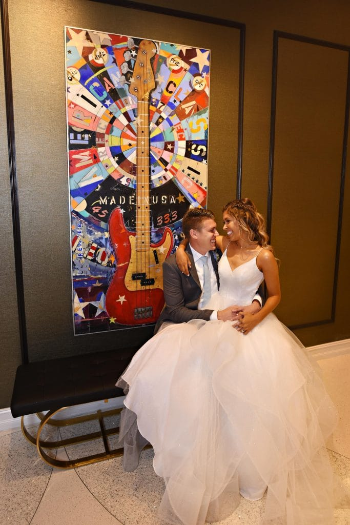 bride and groom posing next to colorful artwork of guitar.