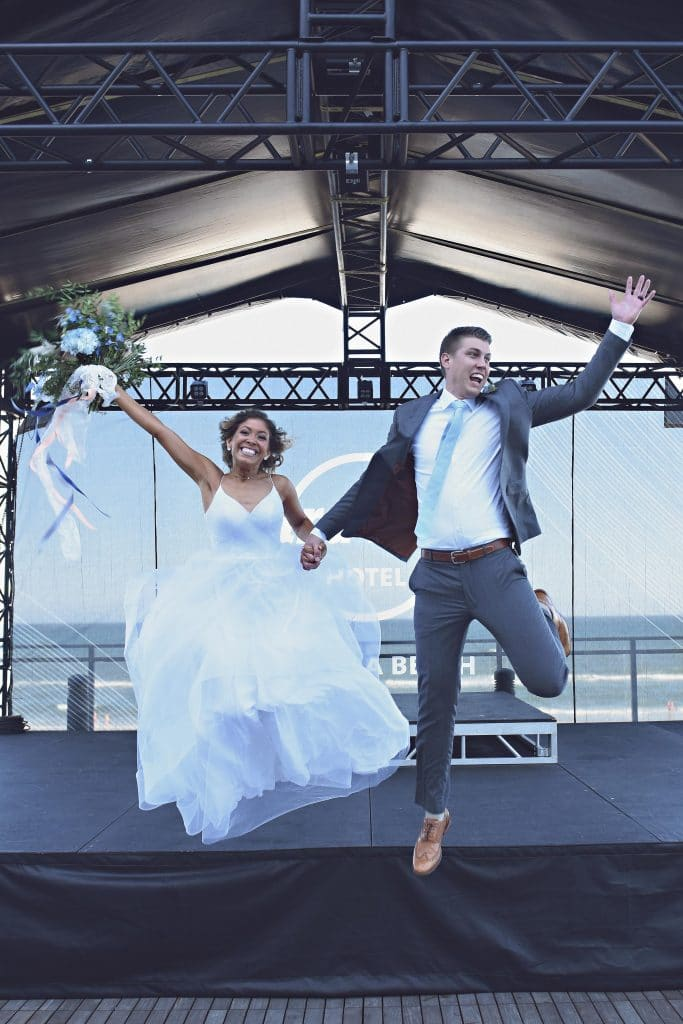 bride and groom leaping off stage