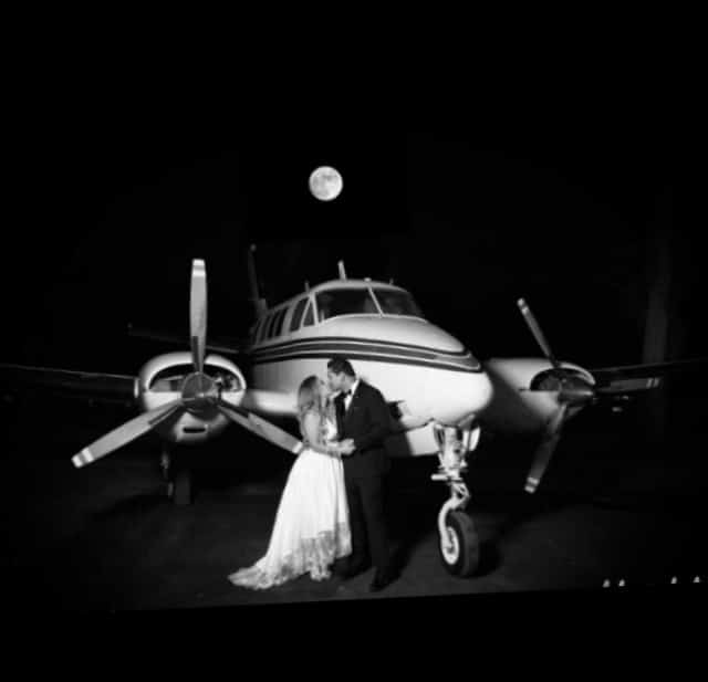 Cedar Knoll Events - bride and groom kissing in front of small plane
