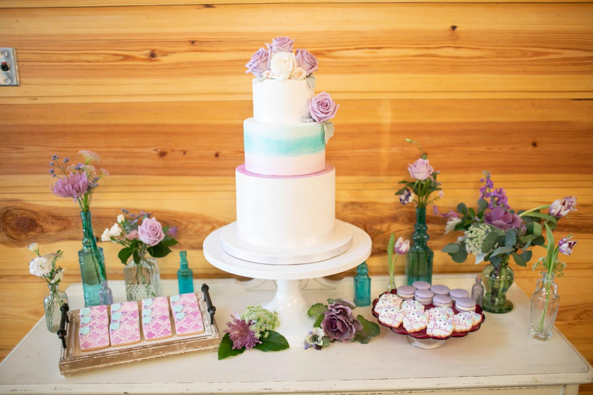 Everything Cake - wedding cake next to cookies and macarons on dessert table.