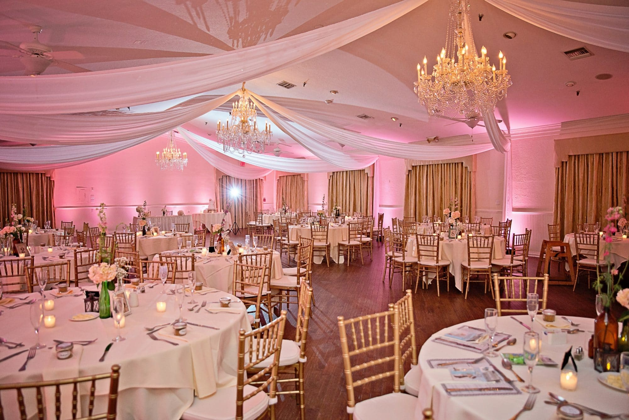 Beautiful indoor wedding reception venue with pink uplighting and white drapery on ceiling.