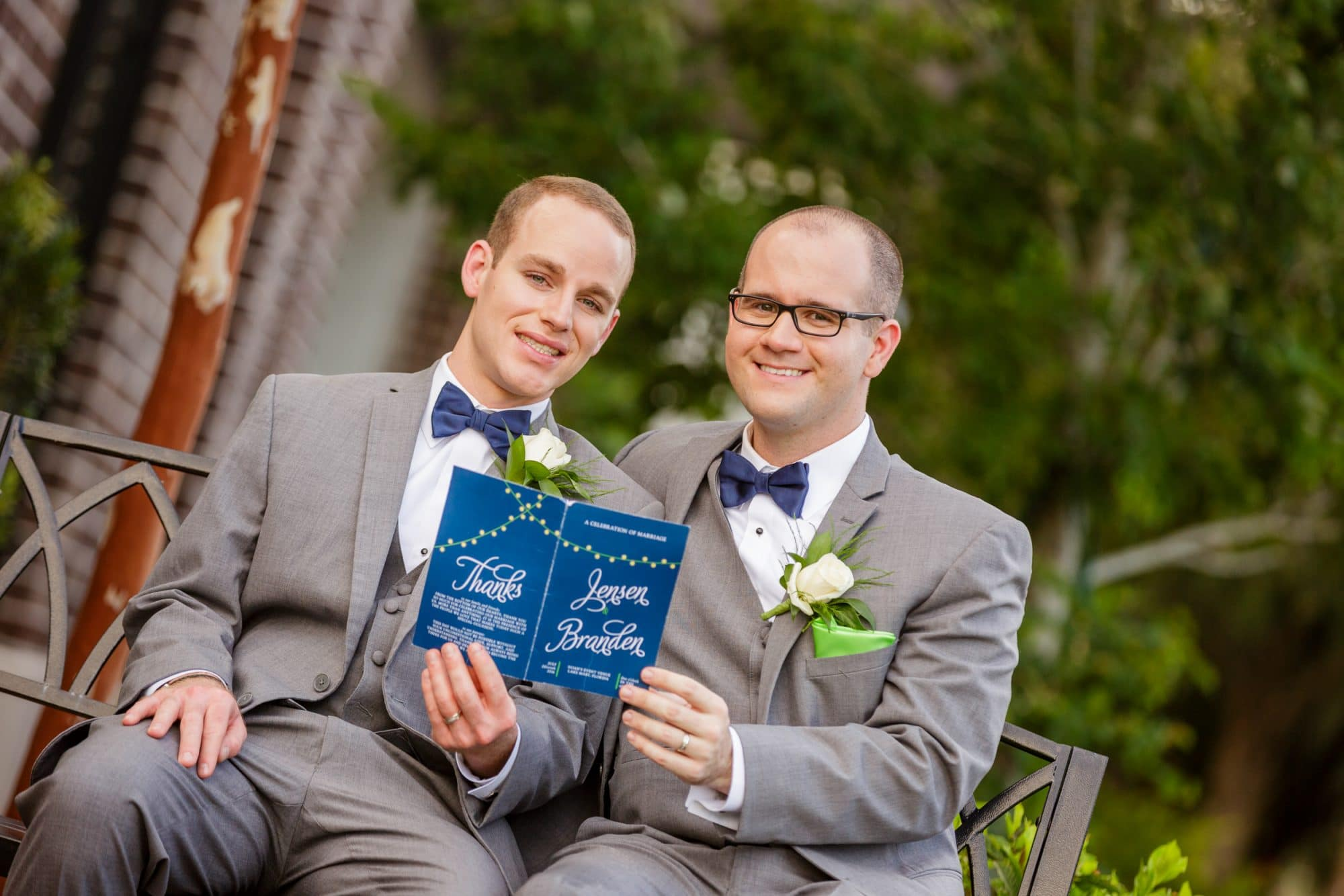 Steven Miller Photography - same sex couple holding up wedding invitation with thank you note