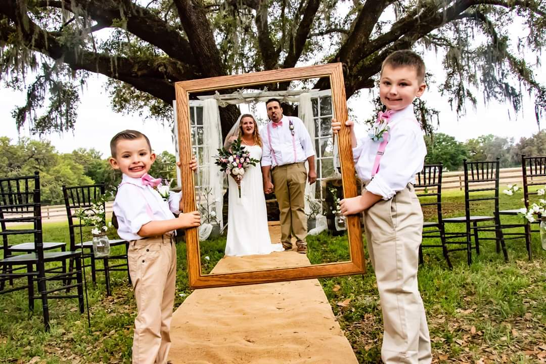 TrueHeart Ranch - two boys holding frame for bride and groom.