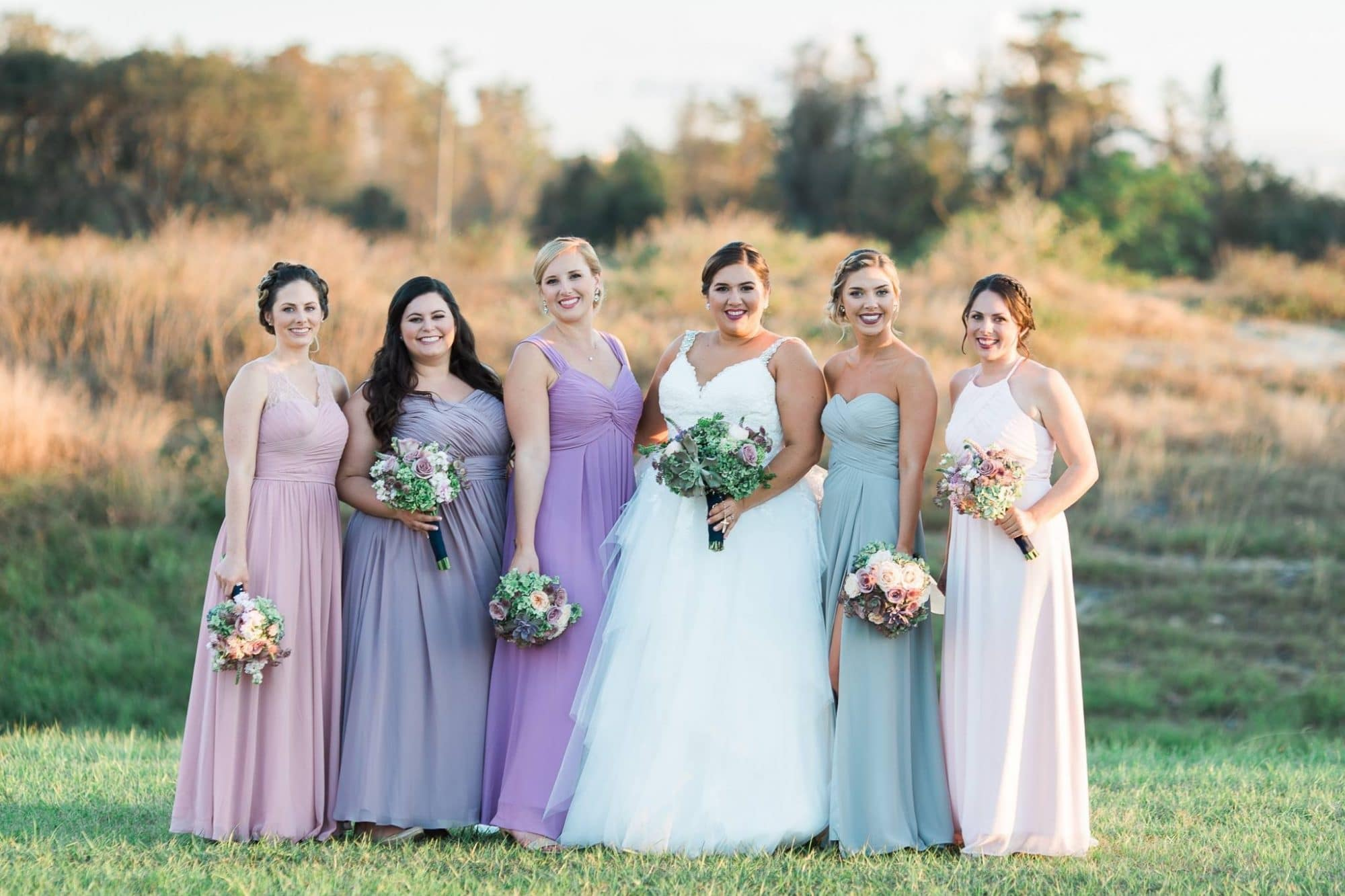 Bride surrounded by bridesmaids in different colored dresses