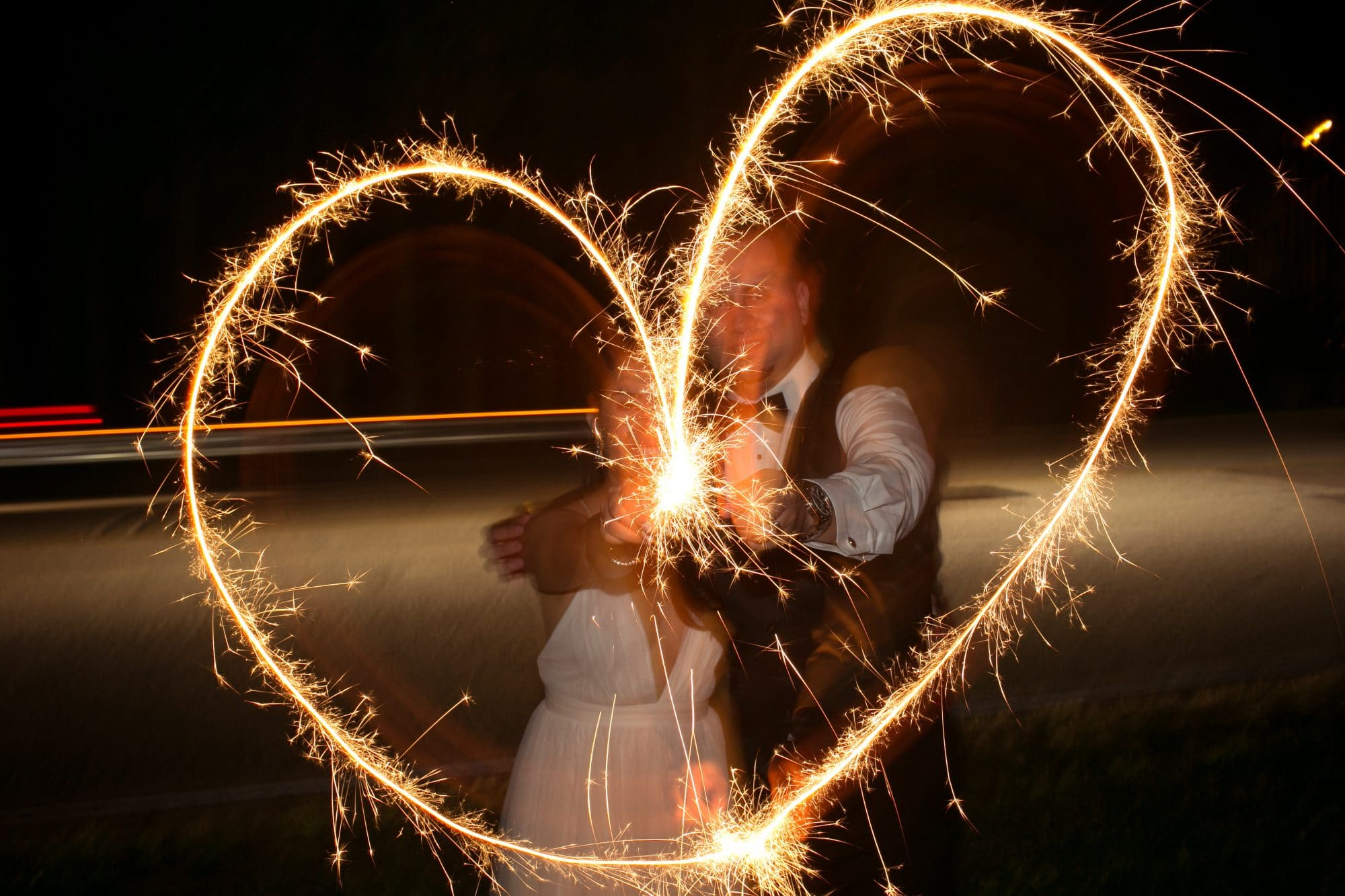 newlyweds making heart shape with sparklers