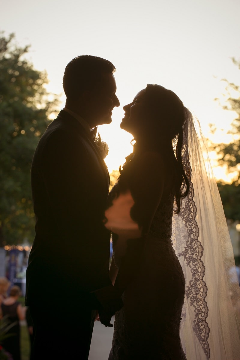 bride and groom silhouetted by setting sun