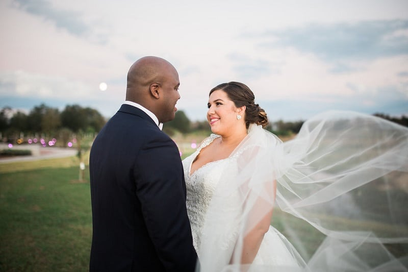 Bride and groom looking at each other while wind tosses bride's veil