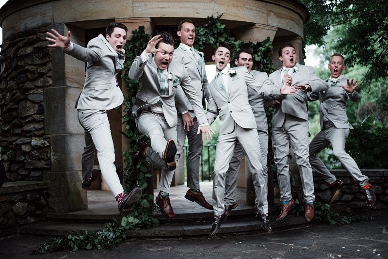 action shot of groom and groomsmen jumping