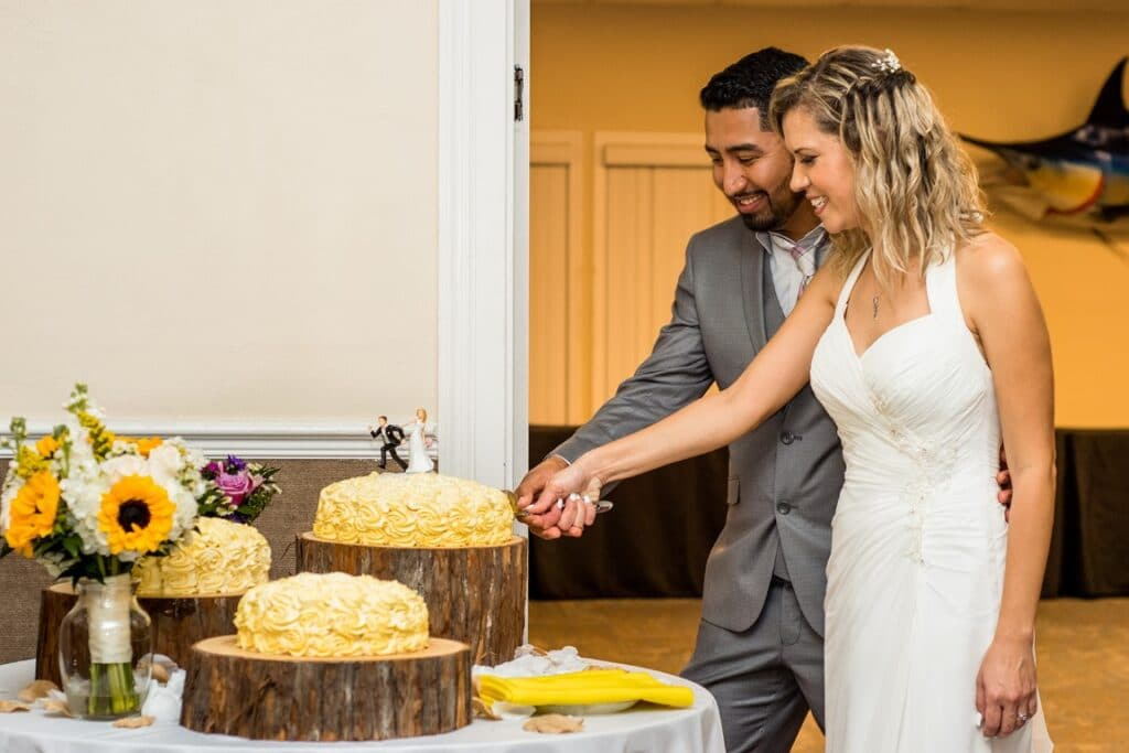 riverside-pavilion-Couple cutting wedding cake on wood stand