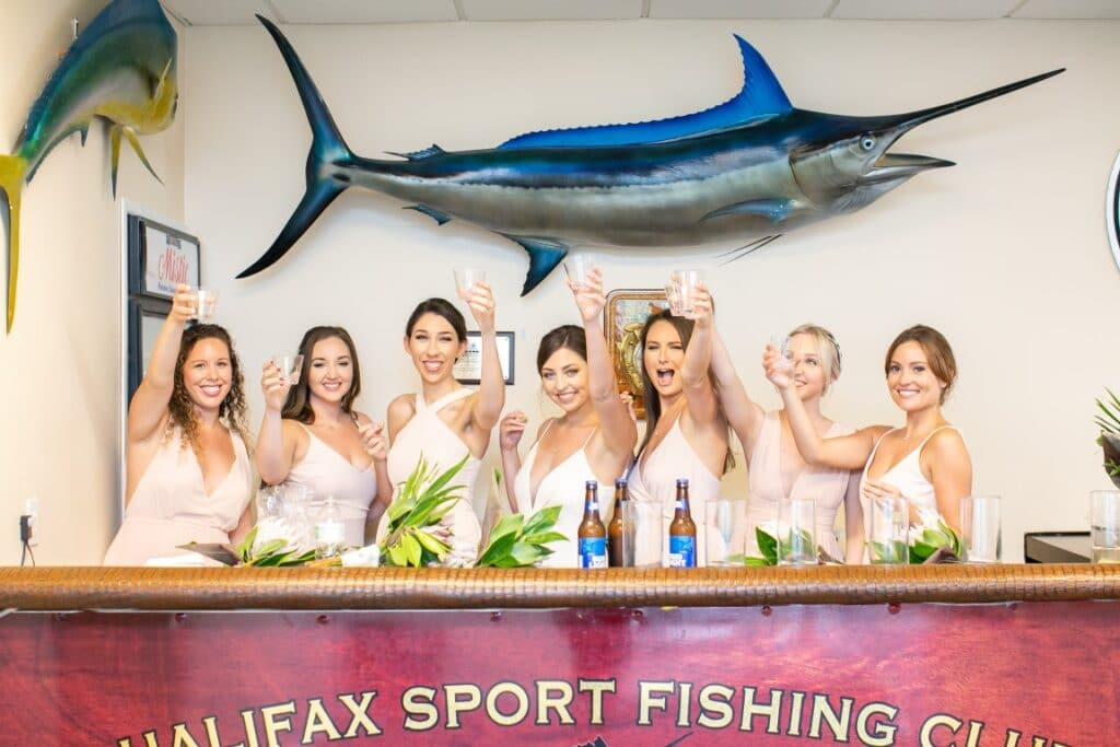 riverside-pavilion-Bridal party raising a glass in front of a marlin