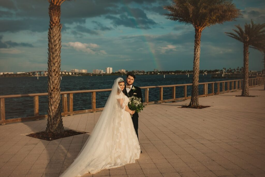 riverside-pavilion-Bride and Groom standing on boardwalk with Rainbow in sky