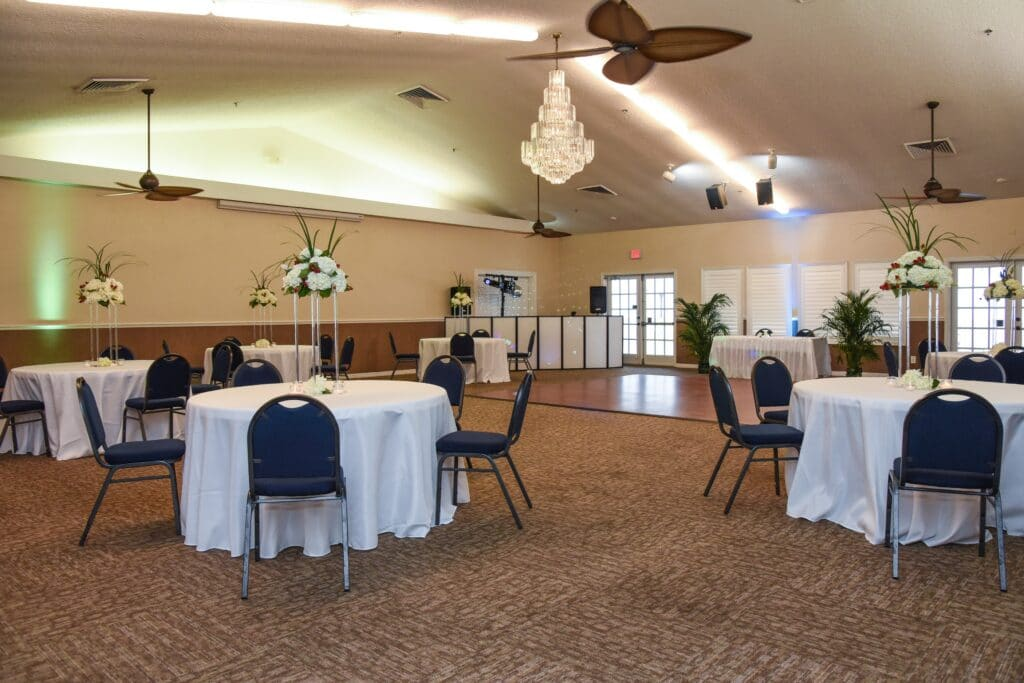 inside of Riverside Pavilion with dance floor and large DJ booth surrounded by several tables and tall flower centerpieces
