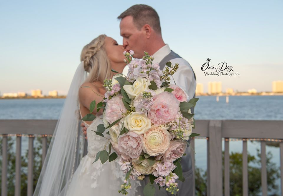 bride and groom kissing and holding flower bouquet outside of Riverside Pavilion overlooking water
