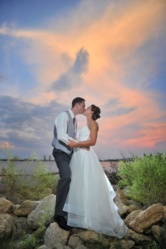 bride and groom kissing outside of Riverside Pavilion on rocks at sunset near the water