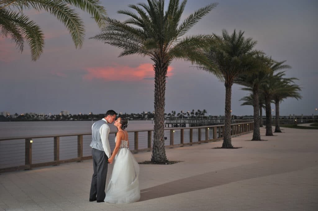 bride and groom kissing at sunset outside of Riverside Pavilion on walkway overlooking the water