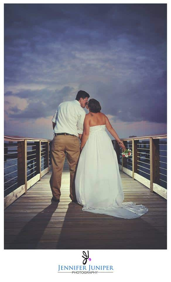 bride and groom kissing while walking down dock at Riverside Pavilion at sunset