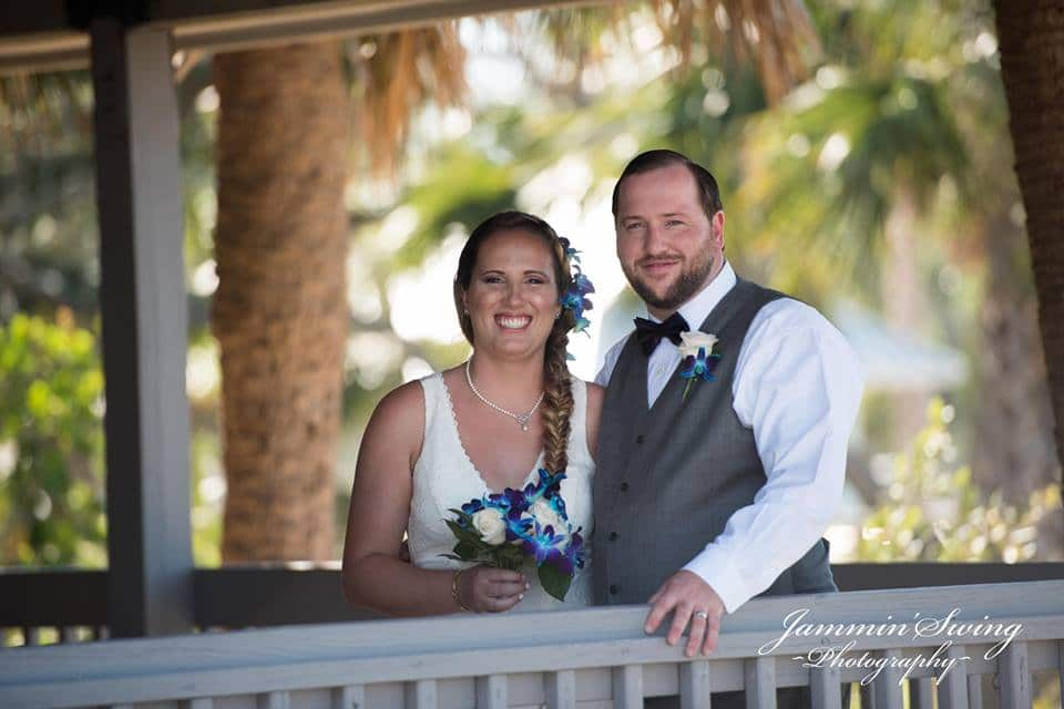 bride and groom standing on covered porch at Riverside Pavilion