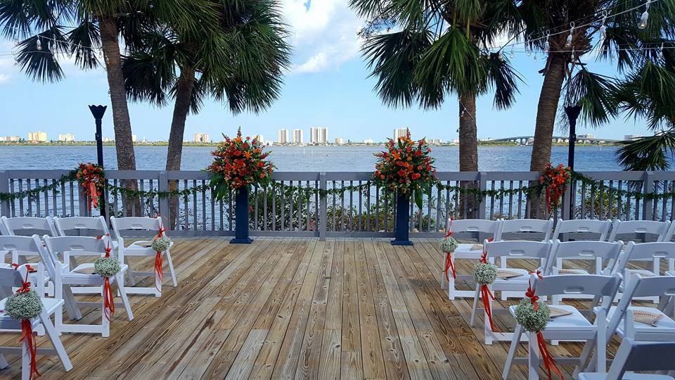 dock patio setup for outside wedding ceremony at Riverside Pavilion, with white chairs and red flowers