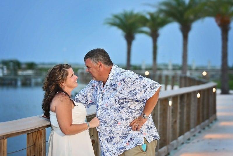 bride and groom standing on dock overlooking water at Riverside Pavilion