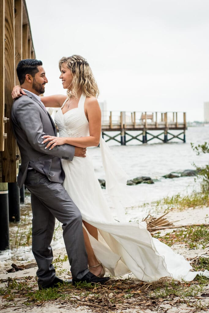 bride and groom embracing on sand at edge of water underneath dock at Riverside Pavilion