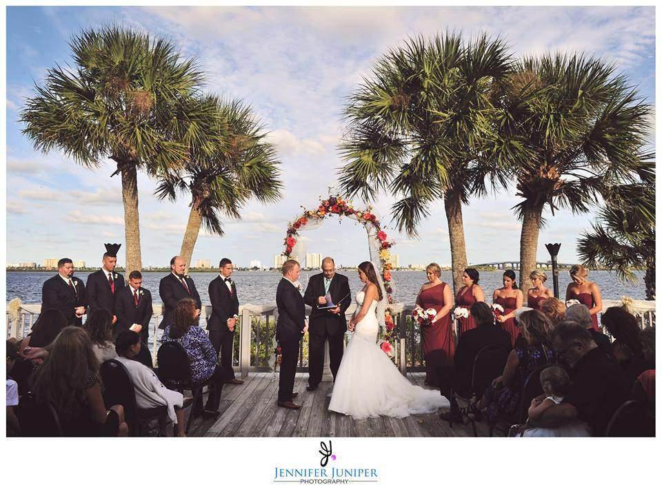 outside wedding ceremony at Riverside Pavilion with bride and groom getting married under palm trees overlooking the water