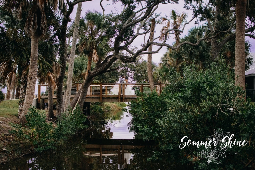 bride and groom kissing while standing on wooden bride over water surrounded by trees outside of Riverside Pavilion