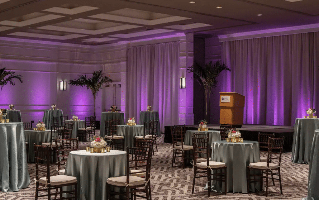 Hyatt-Regency-Orlando-Intnl-Airport-Indoor reception with small round tall tables and beautiful purple uplighting on walls