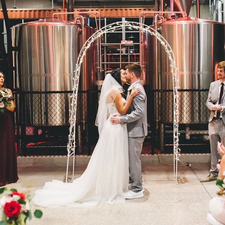 Castle-Church-Brewing-Bride and Groom standing in front of brewery vasts under archway