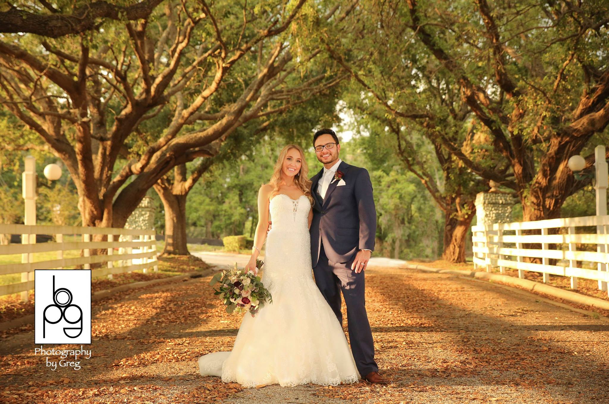 Highland Manor - bride and groom standing in elegant tree-lined path