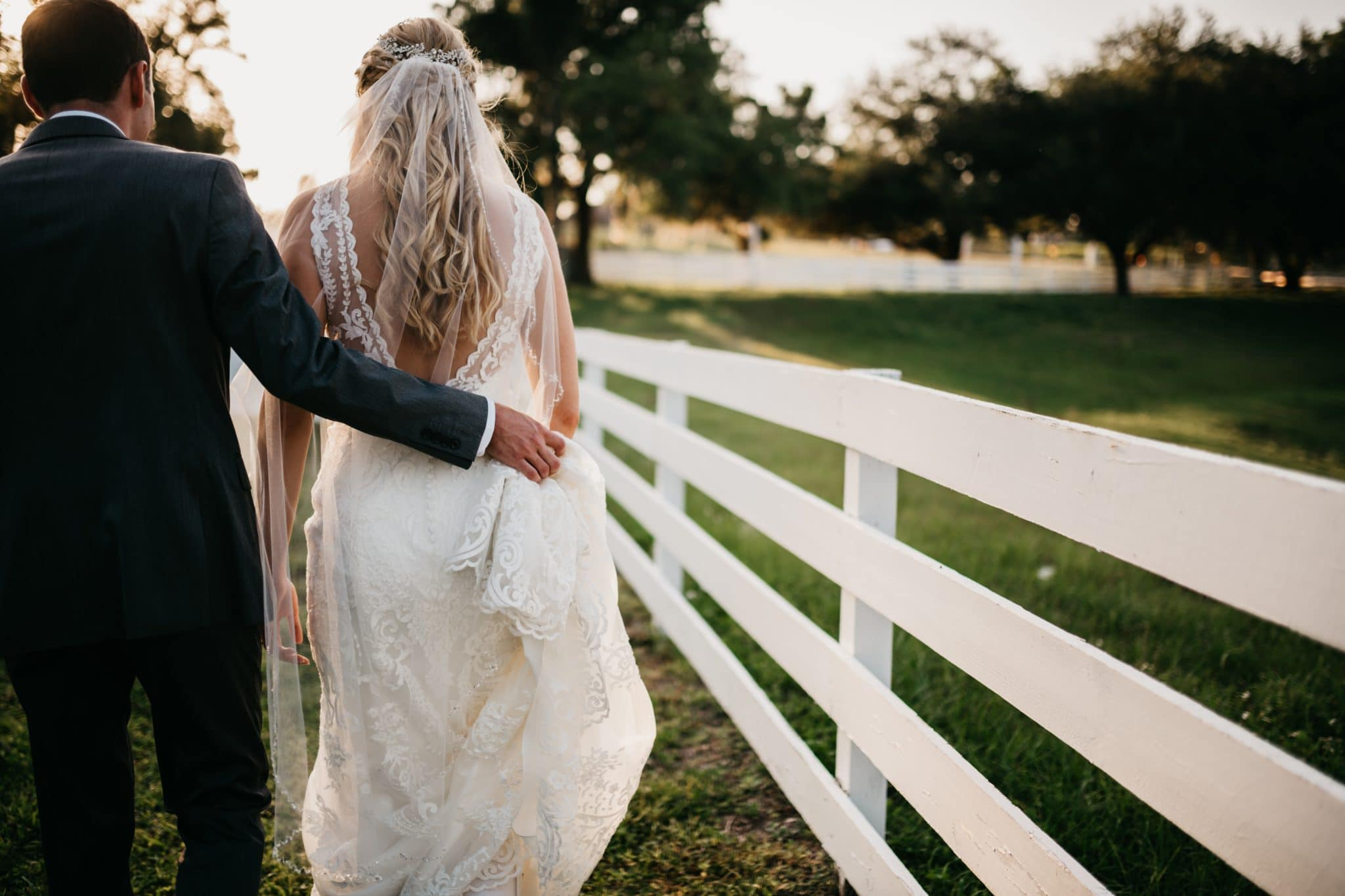 Highland Manor - bride and groom walking into sunset next to white ranch fence.