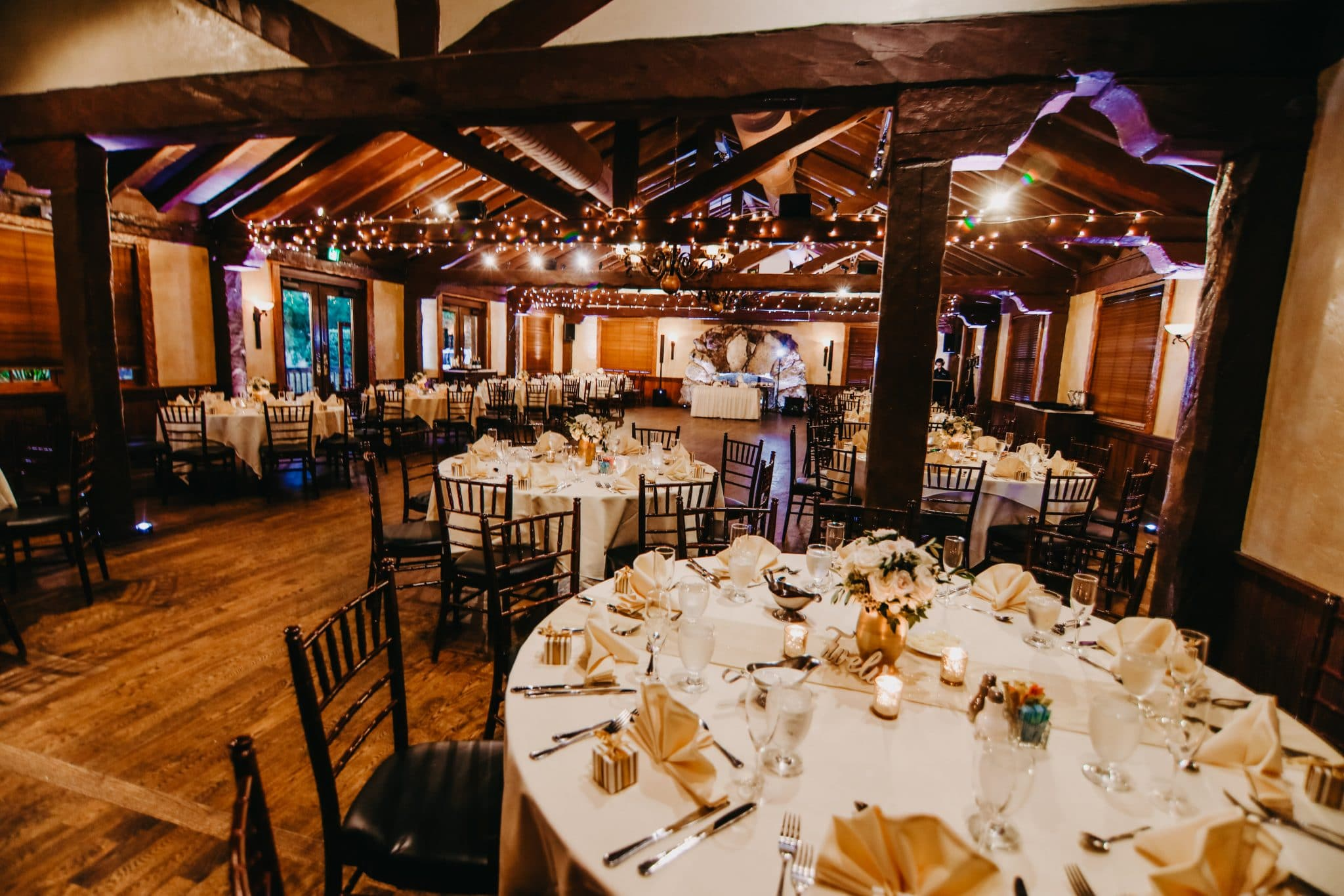 Historic Dubsdread Ballroom - large reception room with exposed beams wrapped in fairy lights
