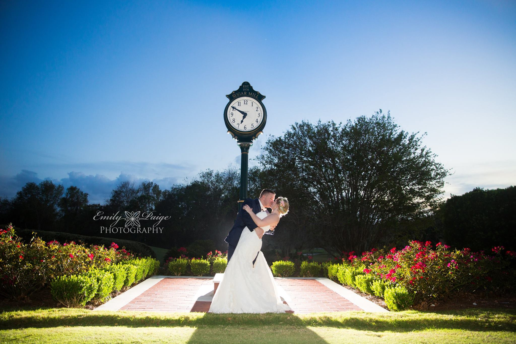 Sugar Mill Country Club - bride and groom kissing in front of large clock