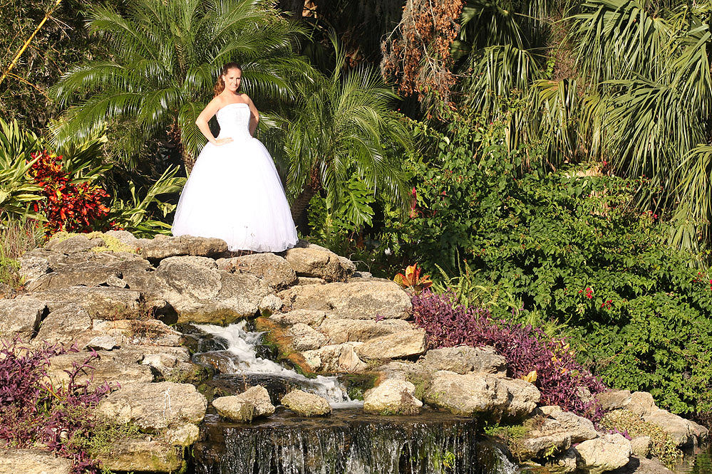 Sugar Mill Country Club - bride next to lush waterfall landscape