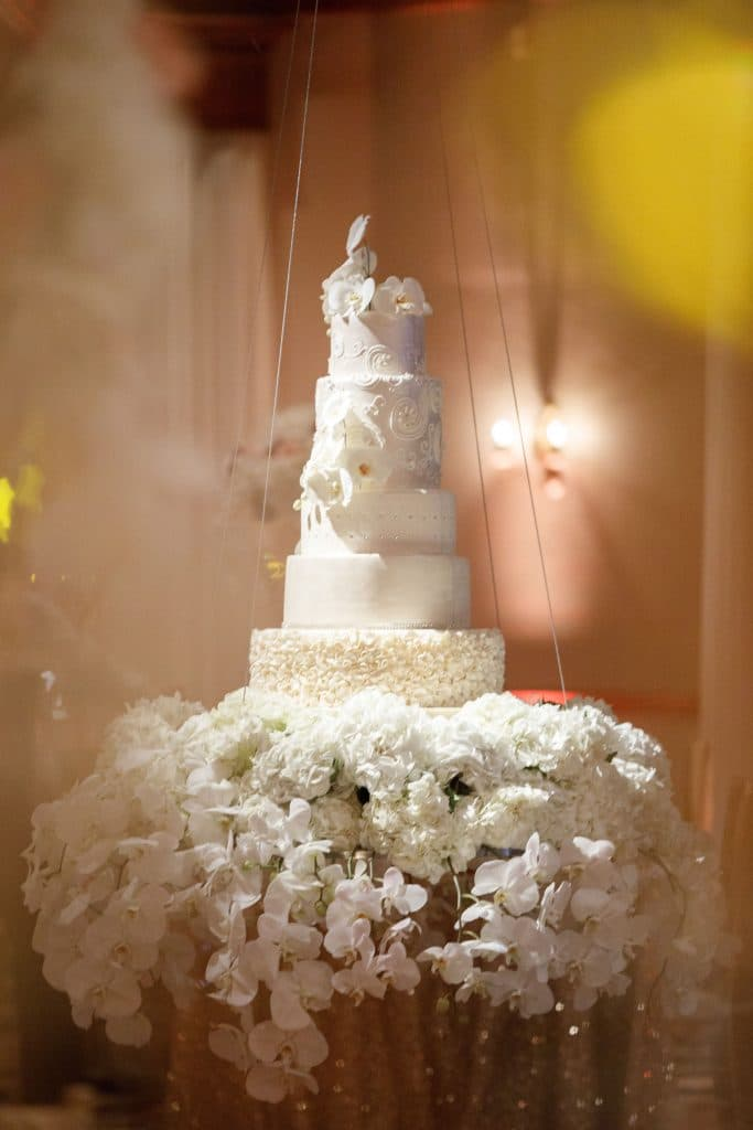 The Cake Studio - all-white five-tiered wedding cake on floral pedestal