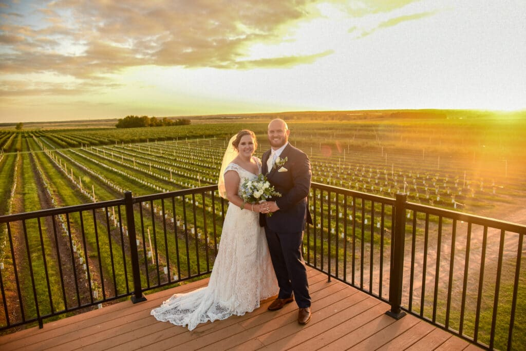 bride and groom standing on an raised patio overlooking the fields of Southern Hill Farms at sunset