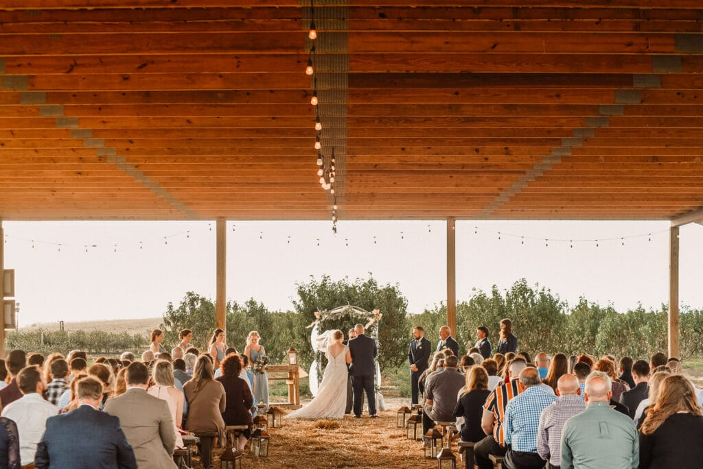 guests watch the bride and groom getting married at an outdoor ceremony at Southern Hill Farms underneath a covered pavilion.