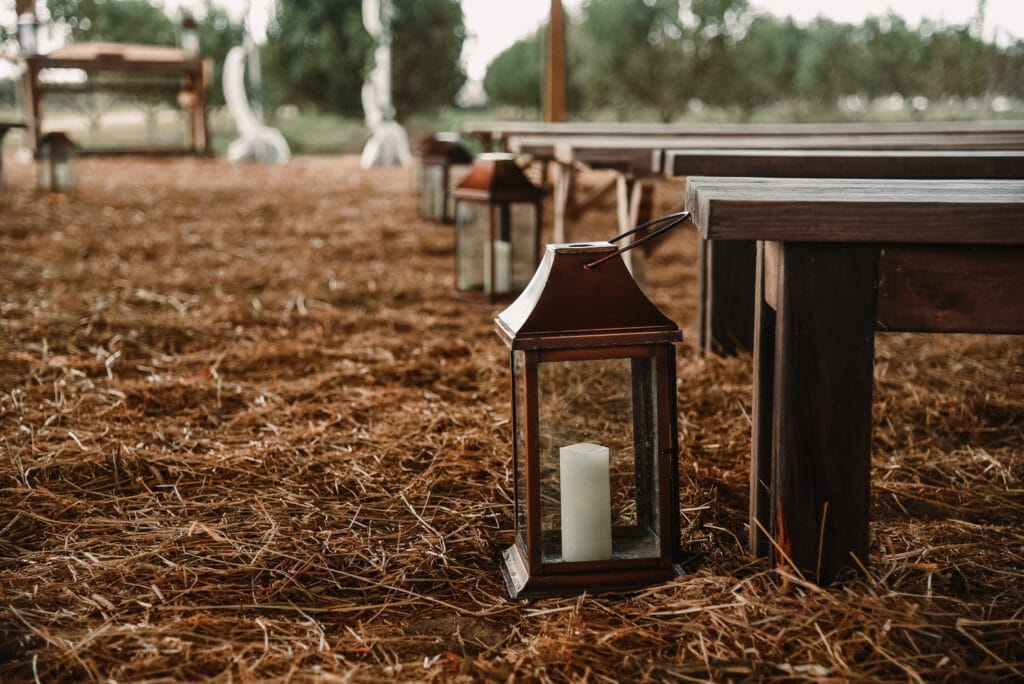 brown wooden benches and rustic lanterns on a bed of straw as decoration for an outdoor wedding at Southern Hill Farms