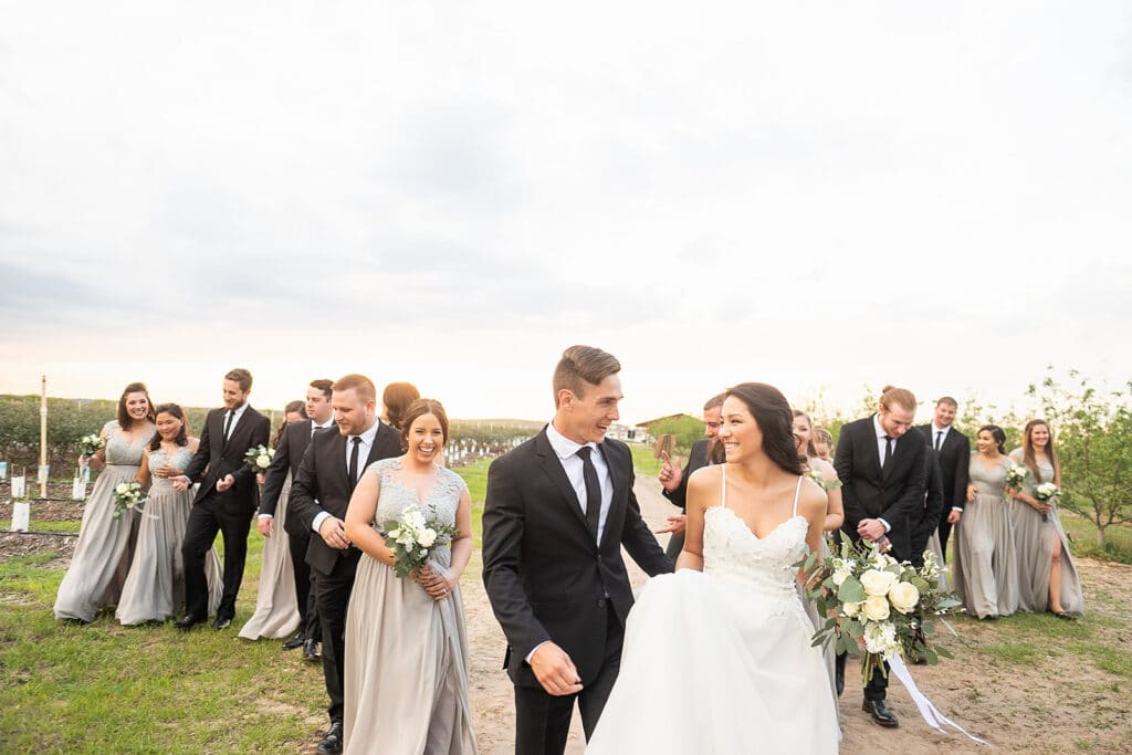 bride and groom smiling with bridal party behind them after their outdoor wedding at Southern Hill Farms