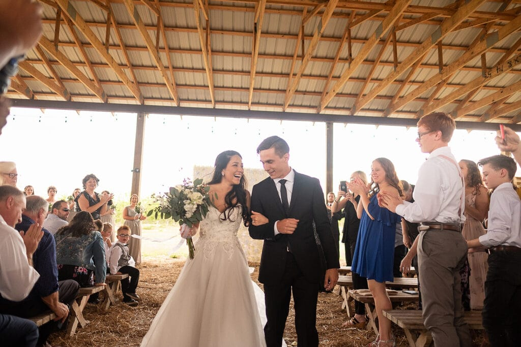 married couple walking down the aisle of their outdoor wedding in a covered pavilion at Southern Hill Farms
