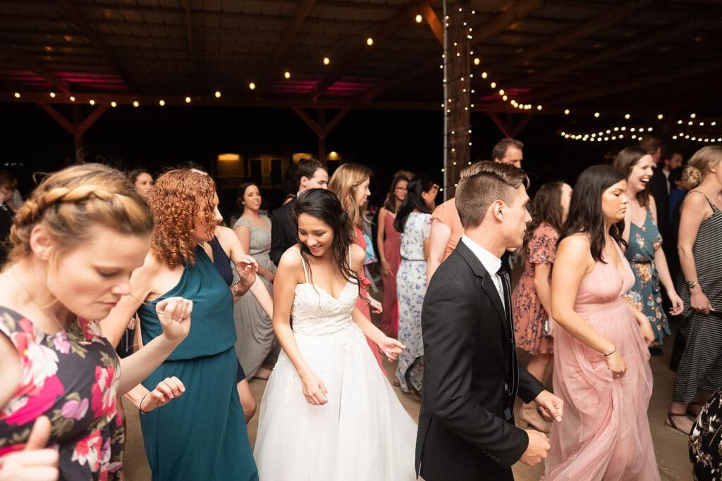 bride dancing with her guests during a nighttime wedding reception under the outdoor pavilion at Southern Hill Farms