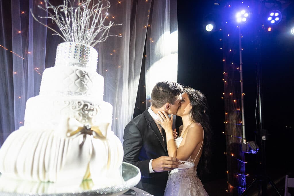 bride and groom kissing while cutting their wedding cake and standing in a spotlight