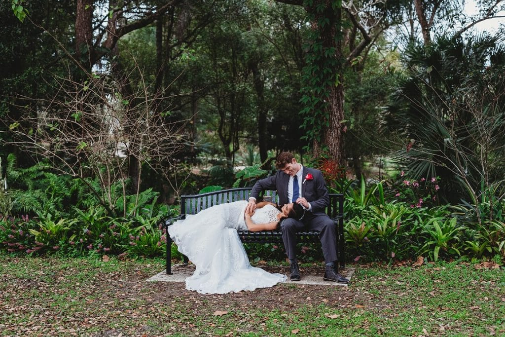 Azalea-Lodge-Mead-Botanical-Garden-bride and groom sitting on iron bench in front of woods