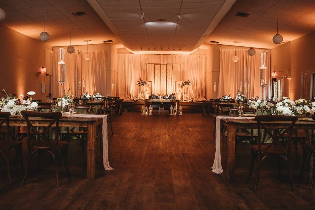 Azalea-Lodge-Mead-Botanical-Garden-Indoor wedding reception area with long wooden tables, peach up lights and long drapes