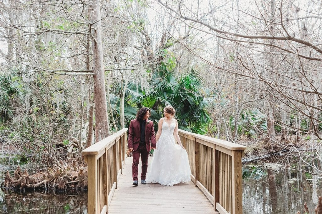 Azalea-Lodge-Mead-Botanical-Garden-Bride and Groom walking down wooden bridge