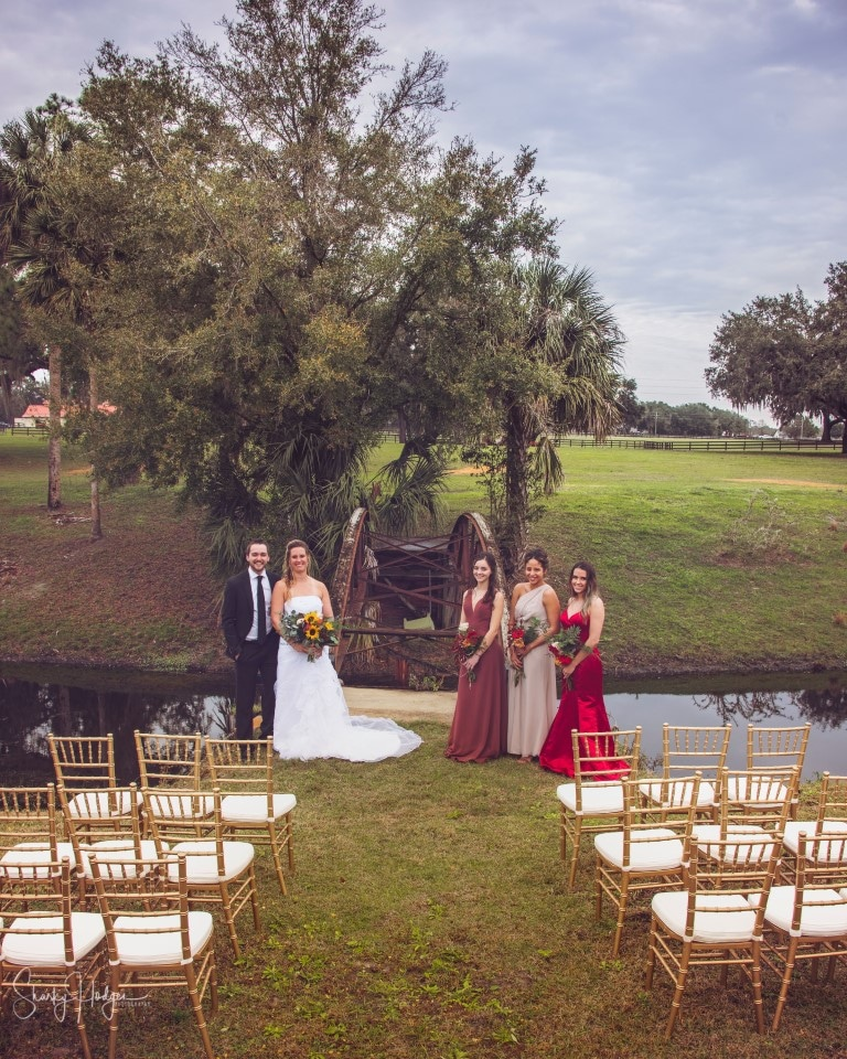 Seas-Your-Day-Island-Happy couple plus bridal party standing at end of isle in front of old wooden bridge