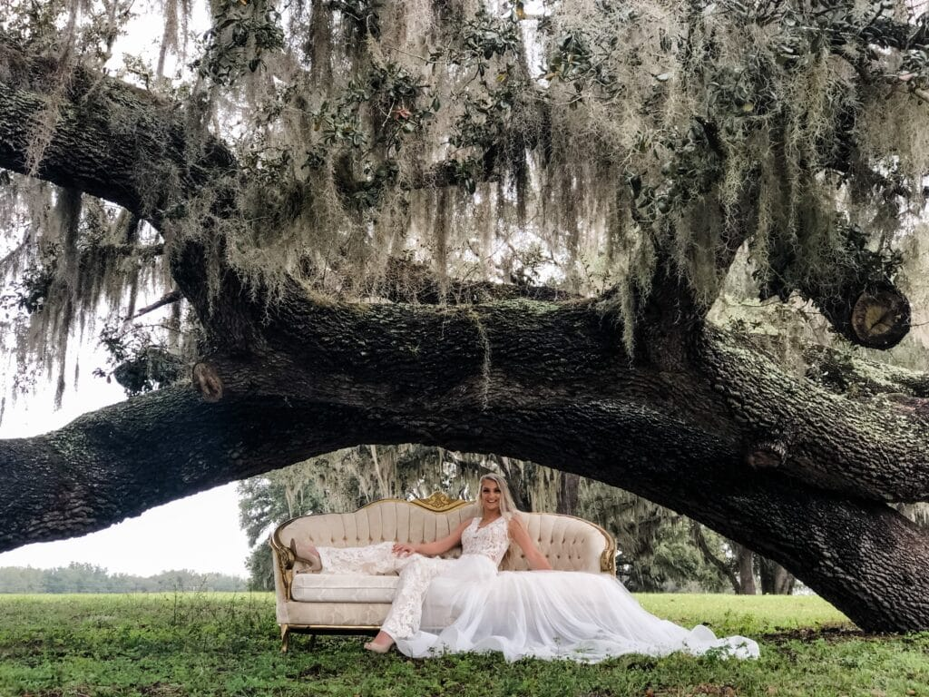 bride in wedding dress sitting on couch under oak tree